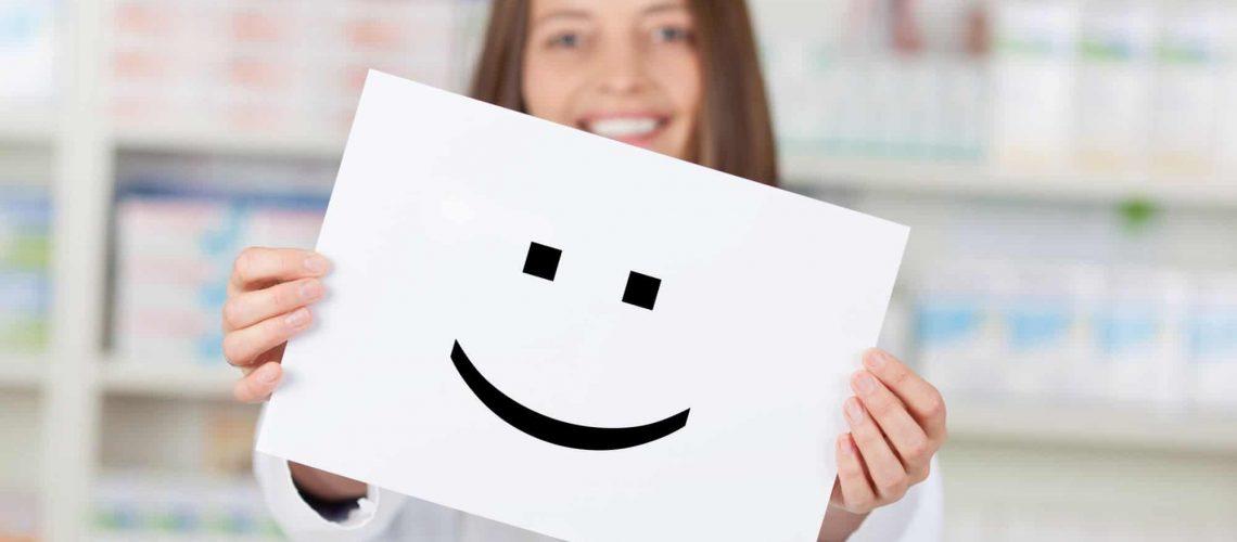 lächelnde apothekerin zeigt smiley